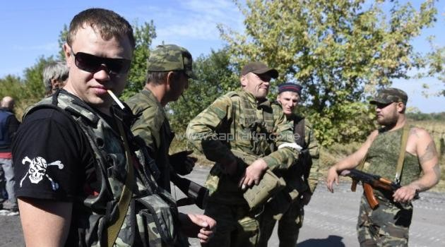 Armed pro-Russian militants take a break at a check point near a front line where shelling continues between pro-Russian forces and the Ukrainian army, in the village of Olenivka, some 30 km south of Donetsk, on September 14, 2014/AFP