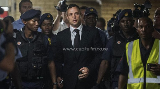South African Paralympic athlete Oscar Pistorius (centre) arrives at the High Court in Pretoria on October 21, 2014/AFP