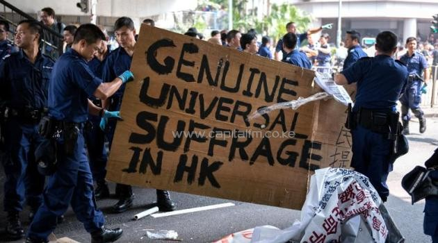 "Police remove a sign that calls for ""Genuine Universal Suffrage in HK"" as they dismantle a pro-democracy protest barricade in Hong Kong, on October 14, 2014/AFP"