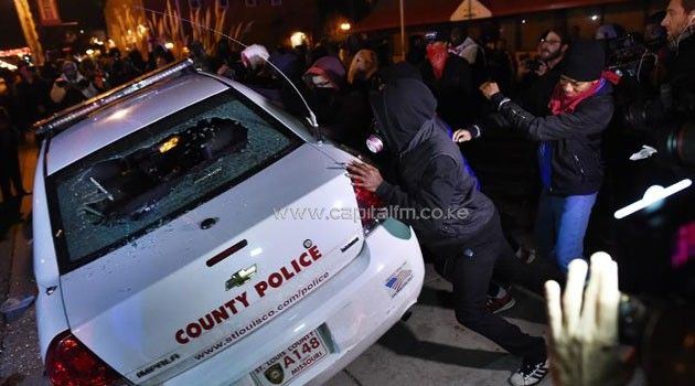 Protesters overturn a police car during clashes with police following the grand jury decision in the death of 18-year-old Michael Brown in Ferguson, Missouri, on November 24, 2014/AFP