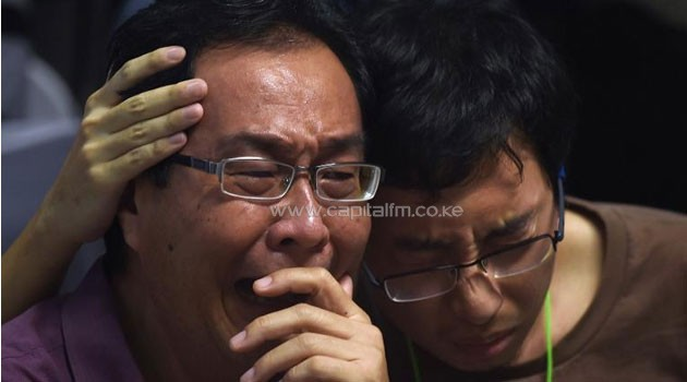 Family members of passengers onboard AirAsia flight QZ8501 react after watching news reports showing a body floating in the Java Sea, while waiting at a crisis-centre set up at Juanda International Airport in Surabaya. Photo/AFP