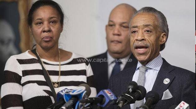 Rev. Al Sharpton (R) is joined by Esaw Garner (L), Eric Garner's widow, as he speaks at a press conference denouncing the shooting deaths of two New York City police officers, on December 21, 2014, in New York City/AFP