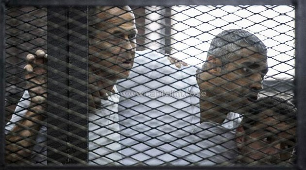 Al-Jazeera reporters Peter Greste (L), Mohamed Fahmy (C) and Baher Mohamed follow their trial proceedings from the defendants cage on June 23, 2014 at the police institute in Cairo/AFP