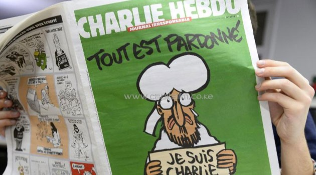 A man in a newsroom in Paris reads the latest issue of French satirical weekly Charlie Hebdo on January 13, 2015/AFP