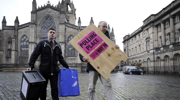 Polling Manager Scott Russel (R) and assistant Ross Clement deliver ballot boxes and a sign to a polling station on The Royal Mile in the centre of Edinburgh on May 6 2015 © AFP