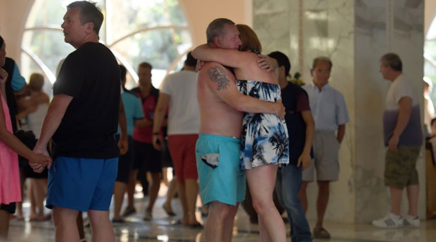 Tourists comfort each other after the mass shooting in the resort town of Sousse, a popular tourist destination 140 kilometers (90 miles) south of the Tunisian capital, on June 26, 2015/AFP