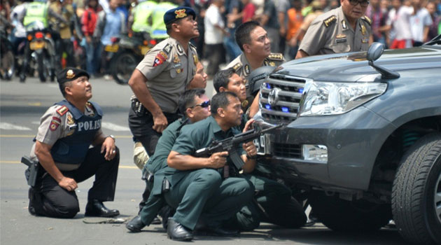 Indonesian police take position behind a vehicle as they pursue suspects after a series of blasts hit the capital Jakarta, on January 14, 2016  © AFP