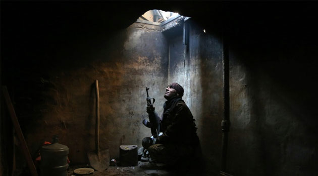 A rebel fighter looks up from his hiding spot in the rebel-controlled area of Arbeen, on the outskirts of the Syrian capital, Damascus on January 29, 2016/AFP