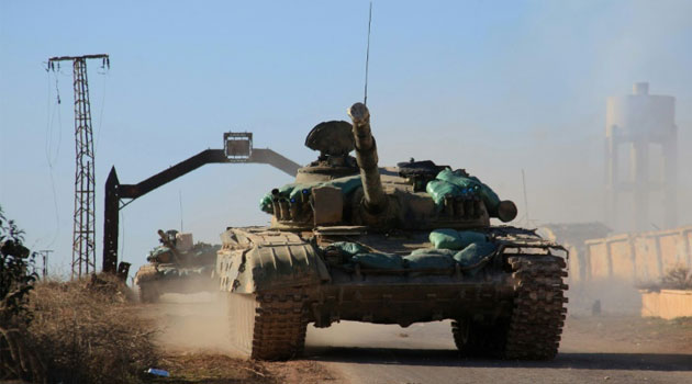 Syrian government tanks drive on the village of Tal Jabin, north of the embattled city of Aleppo/FILE