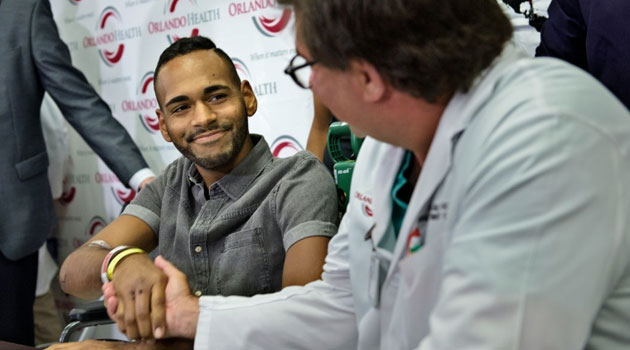 Angel Colon (L), a surviver of the Pulse nightclub mass shooting, shakes the hand of Dr. Sandeep Mukerjee before a press conference at Orlando Regional Medical Center on June 14, 2016 in Orlando, Florida/AFP