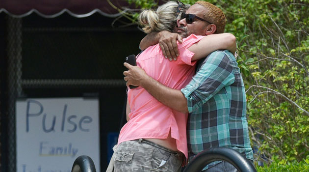 People hug outside of the Beardall Senior Center, currently being used to interview family members of the victims of the Pulse nightclub shooting, on June 13, 2016 in Orlando, Florida/AFP