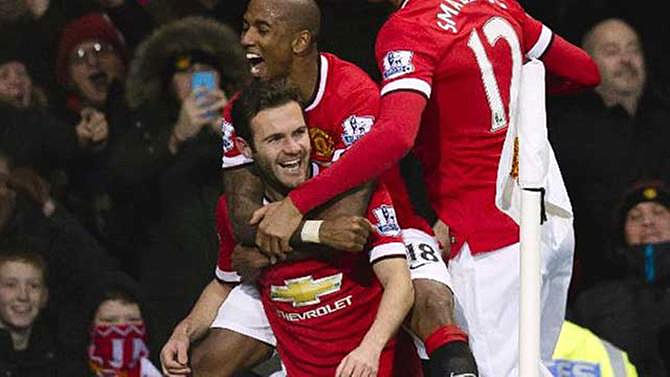 Juan Mata (centre) mobbed by teammates after scoring against Stoke City. PHOTO/File