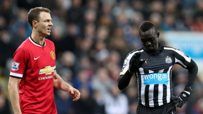 Newcastle striker, Papiss Cisse (left) and Manchester United's Johhny Evans after the pair clashed in an EPL match last season.