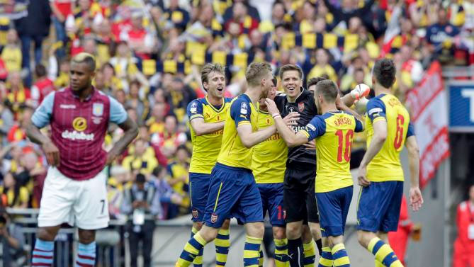 Arsenal players celebrate after winning the English FA Cup final soccer match between Aston Villa and Arsenal at Wembley stadium in London, Saturday, May 30, 2015. Arsenal won the match 4-0.