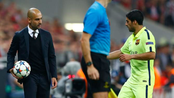 Bayern's head coach Pep Guardiola (L), gives a ball to Barcelona's Luis Suarez during the soccer Champions League second leg semifinal match between Bayern Munich and FC Barcelona at Allianz Arena in Munich.
