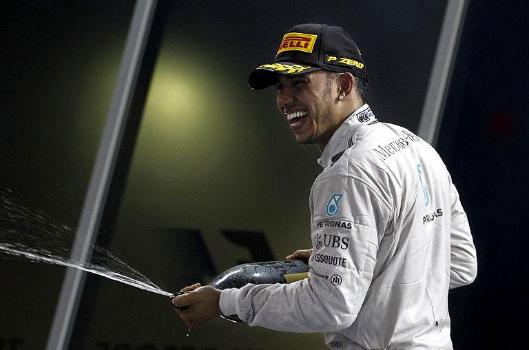 Lewis Hamilton sprays champagne after victory. He has been handed a new 3-year deal at Mercedes.