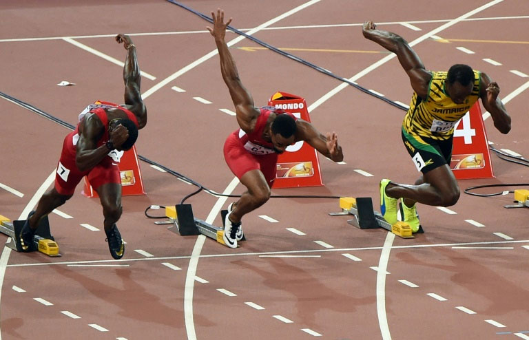 Justin Gatlin (left), Usain Bolt (right) and Tyson Gay compete in the men's 100m final in Beijing on on August 23, 2015. PHOTO/AFP