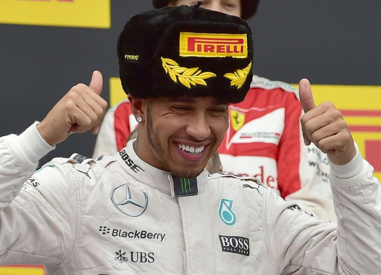 British driver Lewis Hamilton celebrates his victory on the podium after the Russian Grand Prix at the Sochi Autodrom circuit on October 11, 2015. PHOTO/AFP