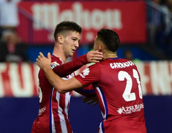 Atletico Madrid's forward Luciano Vietto (L) celebrates with midfielder Yannick Ferreira Carrasco after scoring during a Spanish league football match against Real Madrid at the Vicente Calderon stadium in Madrid on October 4, 2015. PHOTO/AFP
