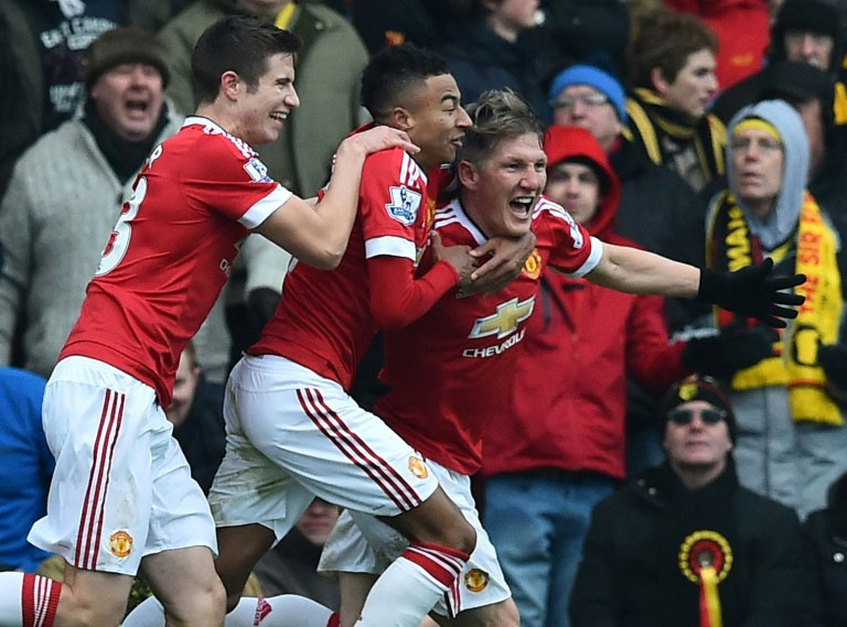 Manchester United's Bastian Schweinsteiger (R) celebrates with teammates Paddy McNair and Jesse Lingard (2nd L) after scoring during the Premier League match against Watford at Vicarage Road Stadium on November 21, 2015. PHOTO/AFP