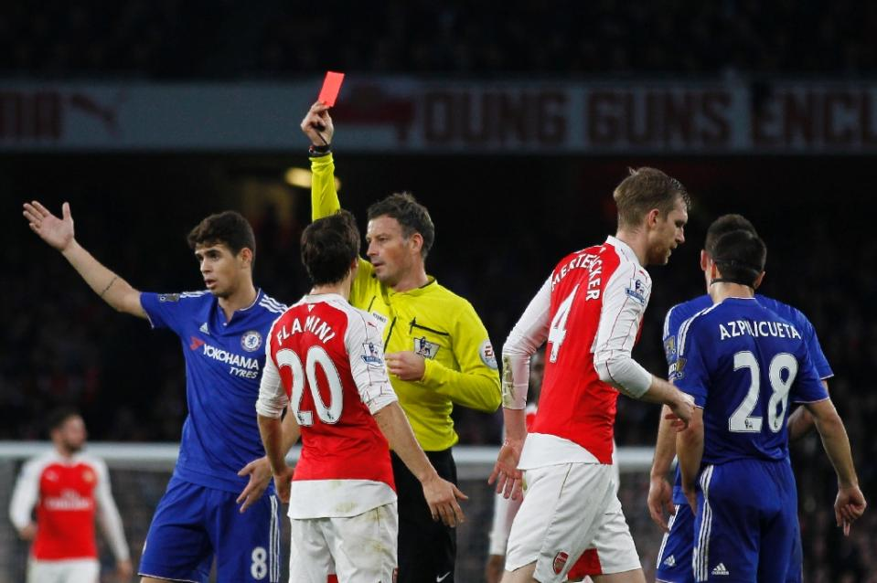 Referee Mark Clattenburg (C) shows a red card to Arsenal's defender Per Mertesacker (2nd R) after his challenge on C