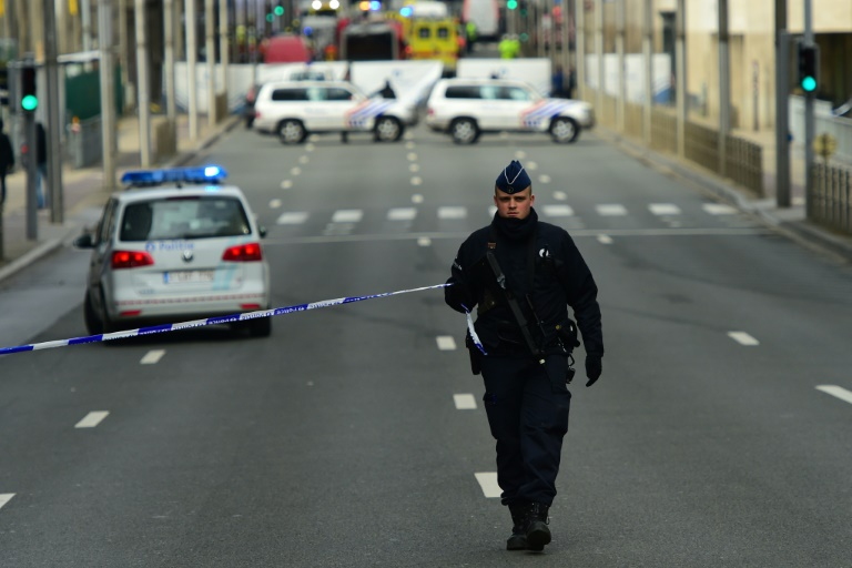 A police officer sets up a security cordon near Maalbeek metro station in Brussels on March 22, 2016 after a blast at thie station near the EU institutions caused deaths and injuries. PHOTO/AFP.