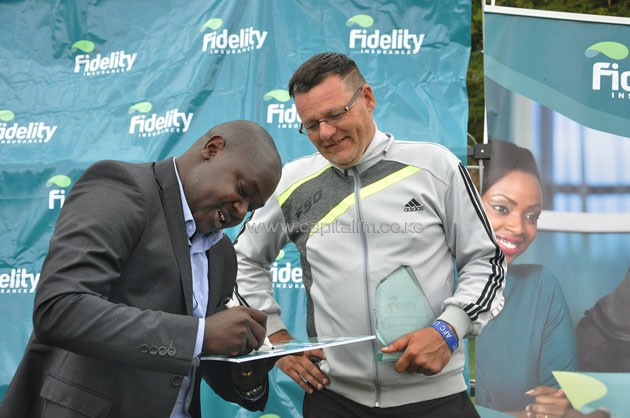 Fidelity Insurance marketing manager Nicholas Malesi (left) signing a cheque for AFC Leopards head coach Ivan Minnaert who was named coach of the month for March.PHOTO/SJAK