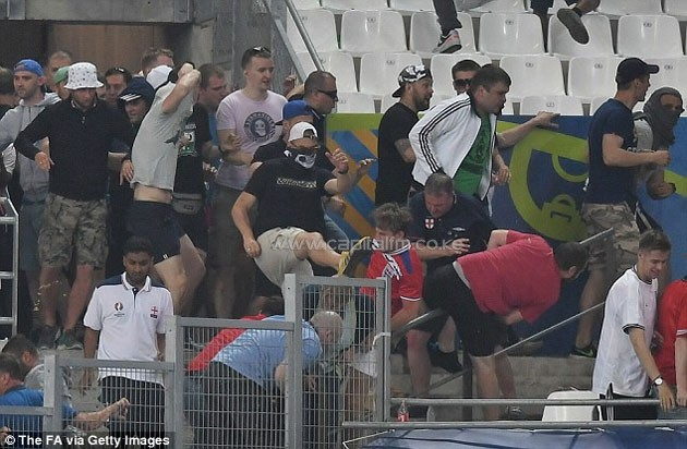 A Russian fan wearing a balaclava rushes towards an England supporter as violence kicked off at full-time.PHOTO/courtesy.
