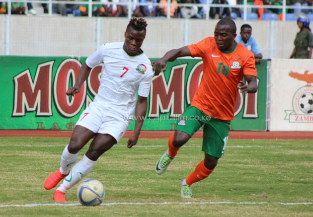 Harambee Stars winger Ayub Timbe on the ball against Chipolopolo player. PHOTO/Timothy Olobulu