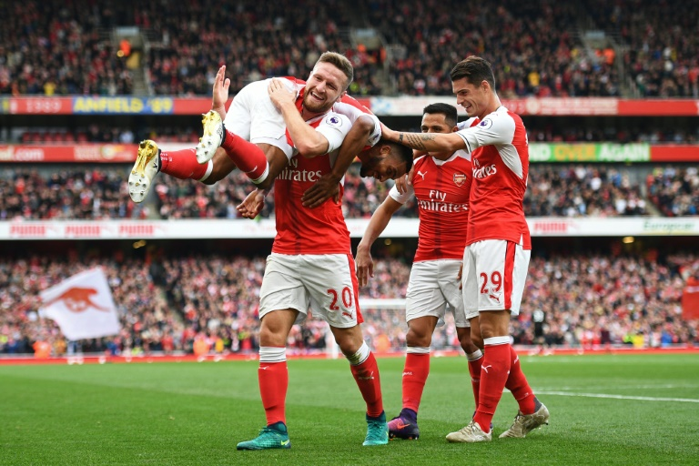 Arsenal's (from L) Theo Walcott celebrates with teammates Shkodran Mustafi, Alexis Sanchez and Granit Xhaka after scoring a goal during their English Premier League match against Swansea City, in London, on October 15, 2016