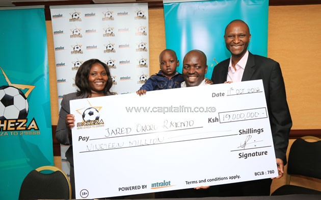 Jared Ratemo alongside his wife and son receiving the Sh19mn cheque from mCHEZA representatives