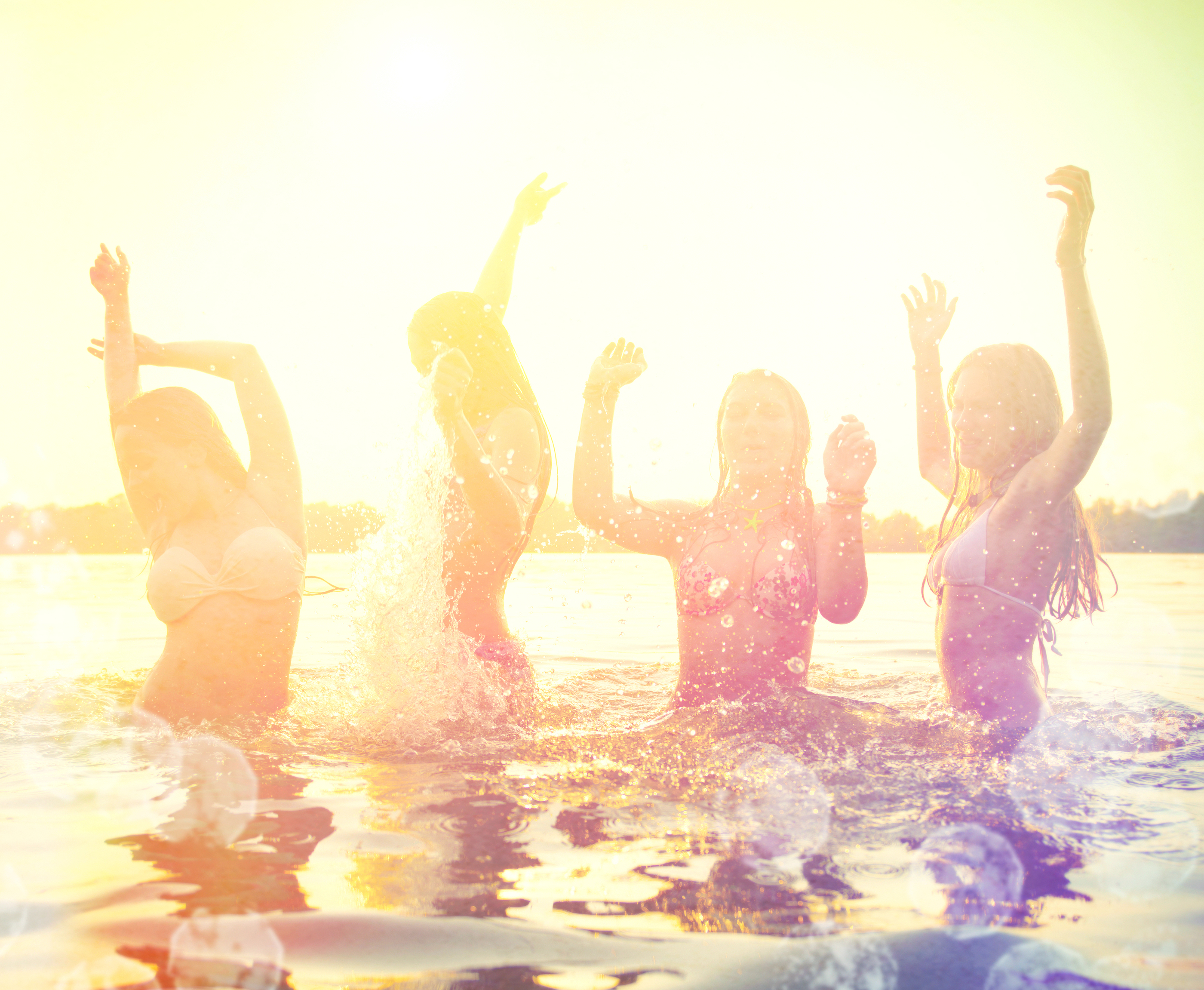 Group of happy teen girls playing in water at the beach on sunse